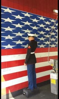 A man in uniform saluting an American flag painted on a wall inside Best Transmission in Jacksonville, FL